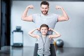 Chlapec s mladým mužem, ukazuje svaly