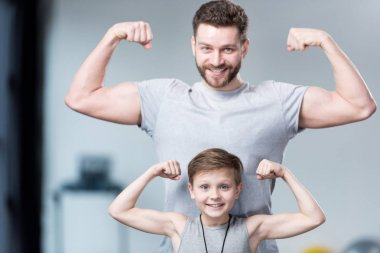 Boy with young man showing muscles