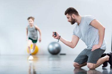 Boy exercising with his coach