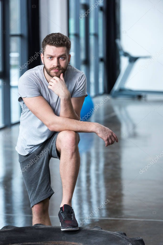 confident man leaning on tyre