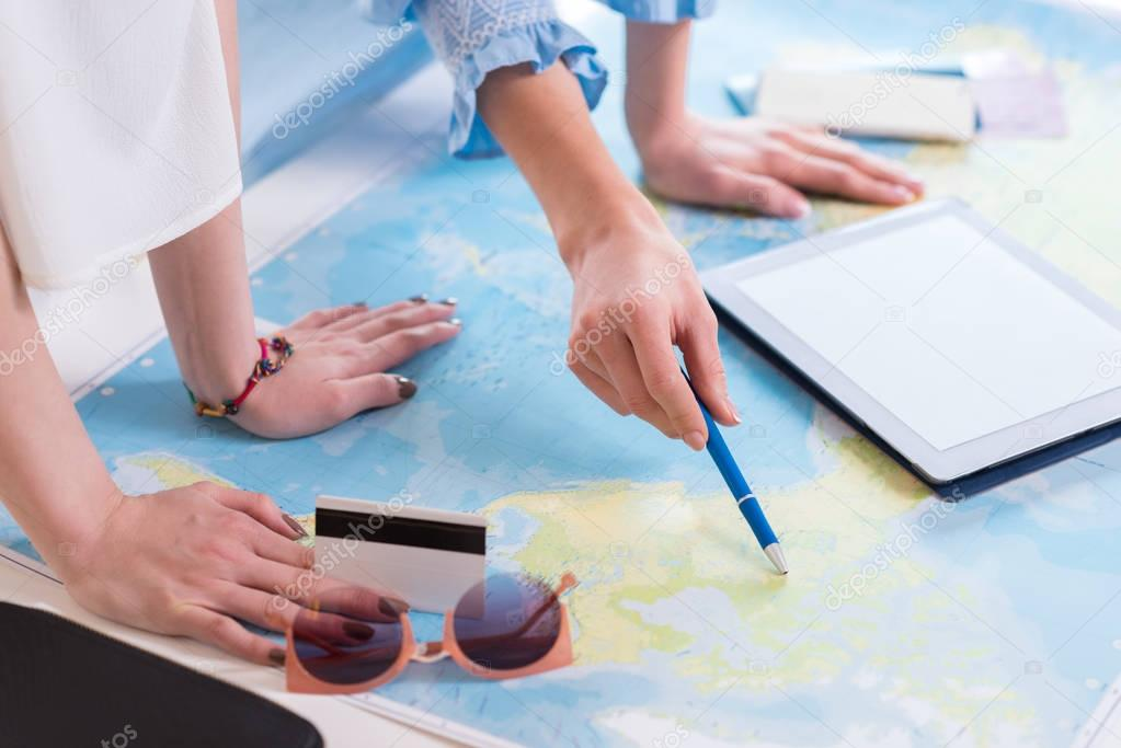 women travelers pointing at world map