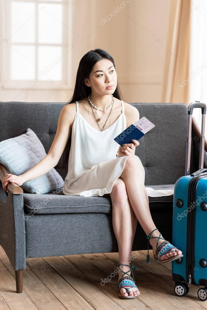 asian woman traveler sitting with suitcase