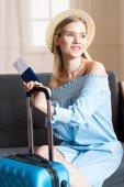 žena cestující sedící kufr a cestovní pas