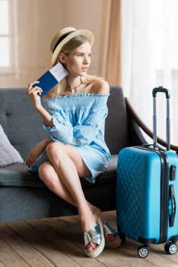 woman traveler sitting with suitcase and passport