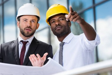 Professional architects in hardhats working with blueprint outside modern building stock vector