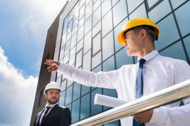 Low angle view of professional architects in hard hats discussing project, successful businessmen concept stock vector