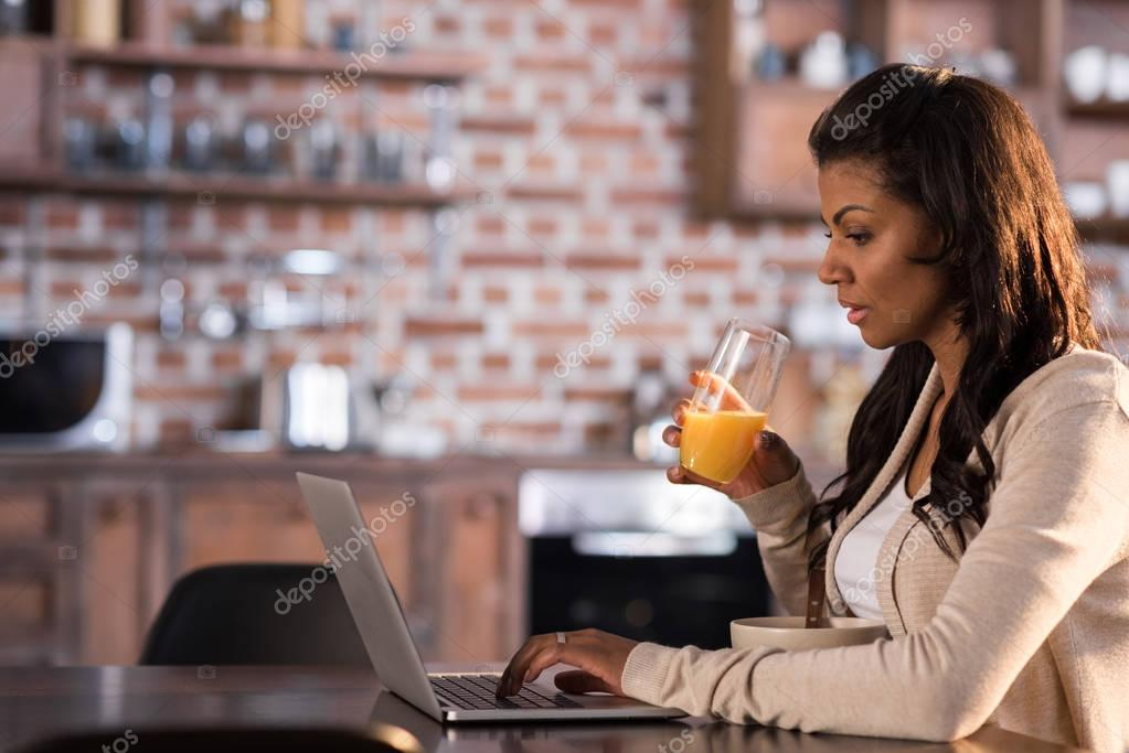 woman having breakfast and using laptop