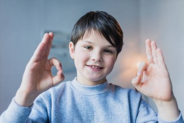 Little boy showing ok sign