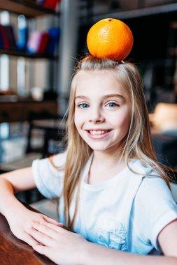 smiling kid girl with orange on head