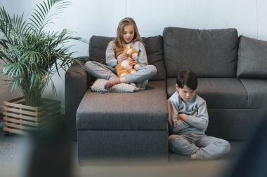 girl with teddy bear and boy sitting