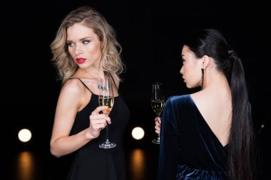 fashionable women holding champagne glasses