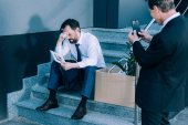 businessman with smartphone photographing fired colleague
