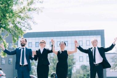 Multiethnic businesspeople holding hands