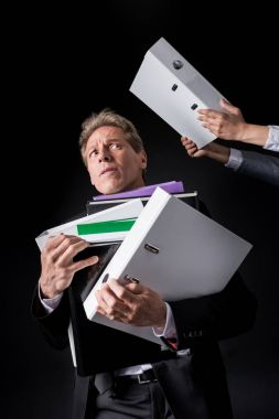 businessman holding pile of folders