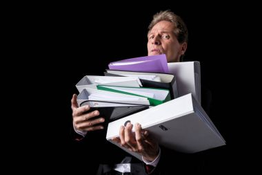Overworked mature businessman holding pile of folders and looking at camera isolated on black stock vector