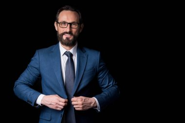 Portrait of confident bearded middle aged businessman in eyeglasses buttoning suit jacket and looking at camera isolated on black stock vector