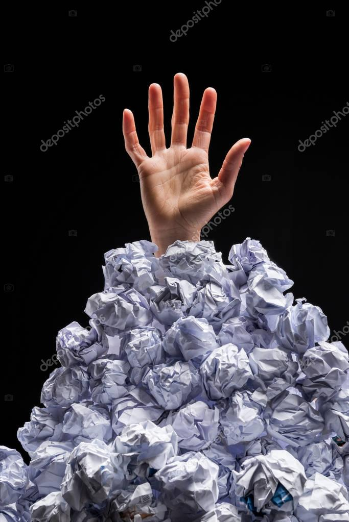 Hand reaching out from heap of papers