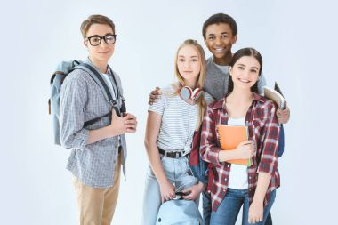 Multiethnic group of teenagers with backpacks looking at camera isolated on white stock vector