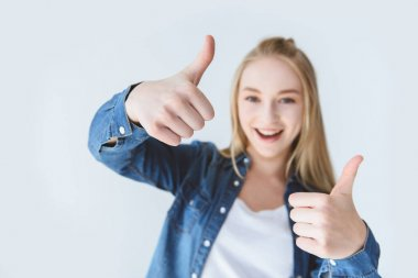 smiling teen girl showing thumbs up
