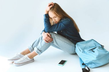 sad teenager with smartphone and backpack