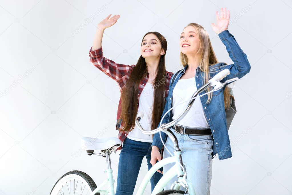 smiling teenagers waving to friend