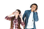 multiethnic teenagers listening music in headphones