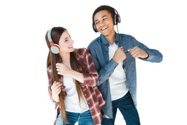 multiethnic teenagers listening music in headphones