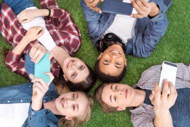 multiethnic teenagers with smartphones