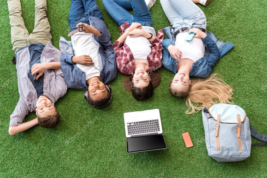 multiethnic teenagers resting on green lawn
