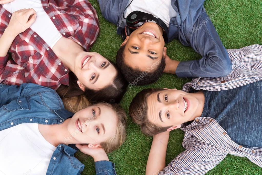 Multiethnic teenagers lying on green lawn