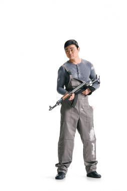 Asian terrorist in dirty overall with rifle isolated on white stock vector
