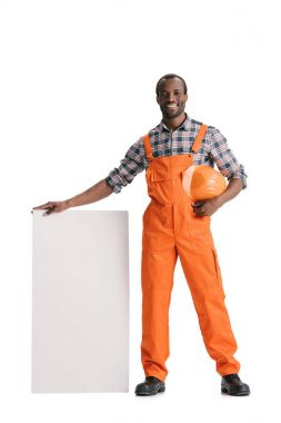 Happy african-american builder with blank white banner isolated on white stock vector