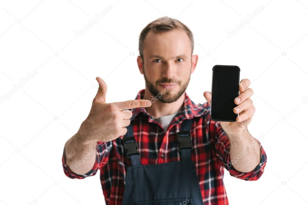 man in overall pointing at smartphone