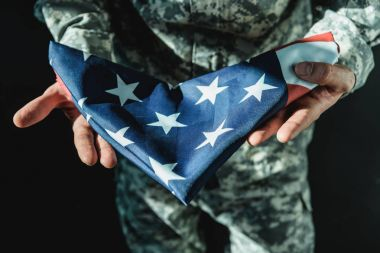 soldier holding folded usa flag