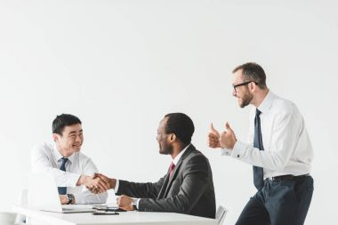 Multiethnic businessmen shaking hands during meeting with colleague showing thumbs up near by isolated on white stock vector