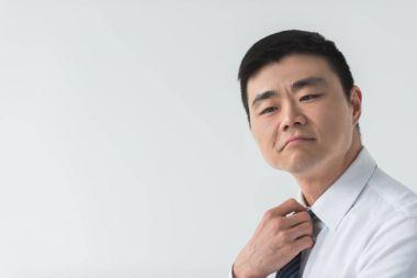 Asian businessman tying necktie