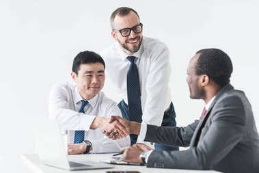 Multiethnic businessmen shaking hands during meeting with colleague standing near by isolated on white stock vector