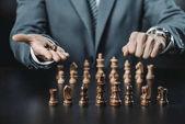 Geschäftsmann und Schachfiguren auf dem Tisch