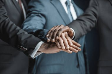 Multiethnic businessmen holding hands