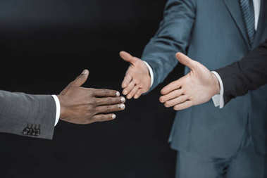 multiethnic businessmen outstretching hands