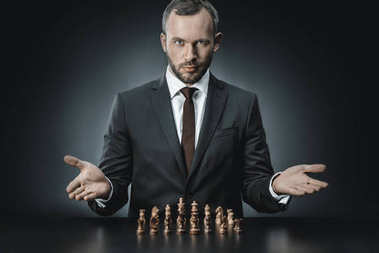 businessman sitting at table with chess pieces
