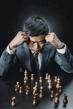 Asian businessman and chess pieces