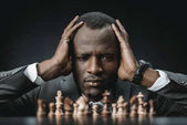 Photo confused african american businessman with chess