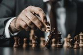 Fotografie Geschäftsmann und Schach Figuren auf Tisch