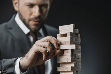 businessman playing blocks wood game