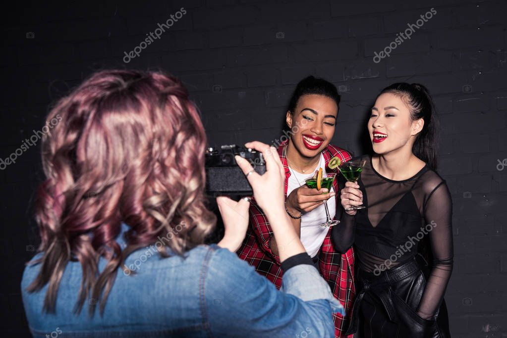 multiethnic women with drinks at party