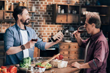 Two middle aged men drinking wine and looking at wine bottle while cooking dinner in kitchen stock vector