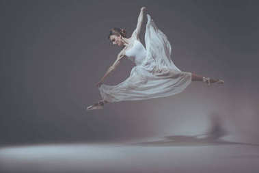 beautiful ballet dancer jumping in white dress