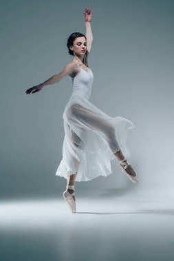 elegant ballerina in white dress dancing in studio
