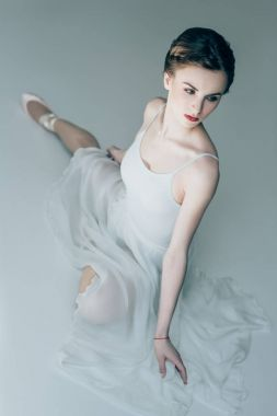 attractive ballerina sitting in white dress and ballet shoes